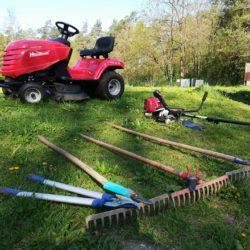 Slika prikazuje zbrano orodje - kosilnico, grablje, klešče za veje ipd.